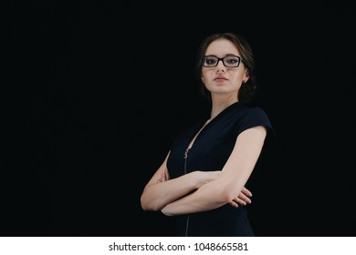Portrait of confident beautiful young business woman with crossed arms standing on black background