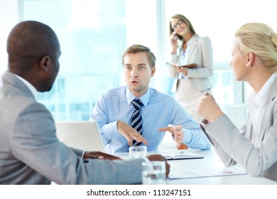 Portrait of confident boss explaining strategy to his partners at meeting
