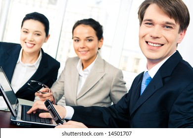 Portrait of confident boss looking at camera on background of cheerful women