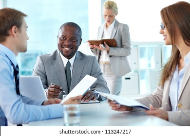 Portrait of confident boss smiling while interacting with employees at meeting
