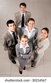Portrait of confident business group standing on the floor and looking at camera with smiles