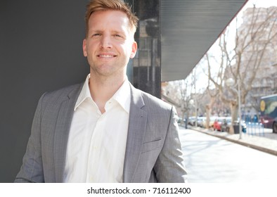 Portrait of confident business man financial district with office buildings, city district, looking and smiling at camera, outdoors. Professional male looking with smart suit, sunny exterior.