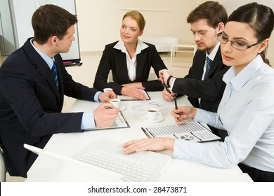 Portrait of confident business partners interacting and working at meeting