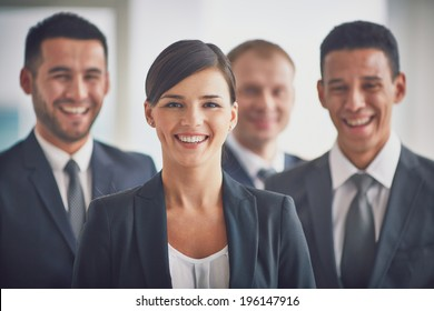 Portrait of confident business partners looking at camera, young smiling woman on foreground
