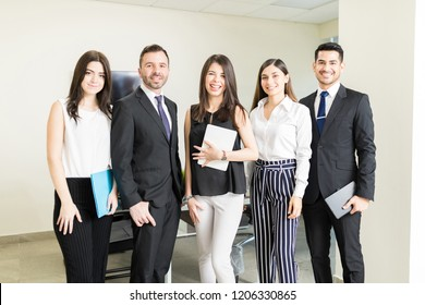 Portrait of confident business team smiling while standing together in office