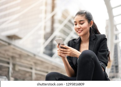 Portrait Confident Business woman using phone at outdoors in city.
