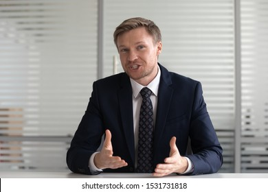 Portrait confident businessman coach wearing suit looking at camera and talking, making video call, mentor coach tutor recording webinar, online course, hr manager holding distance job interview