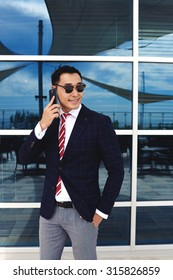 Portrait of a confident businessman dressed in luxury clothes having mobile phone conversation while standing near office window outside, smiling young intelligent men talk on cell telephone outdoors