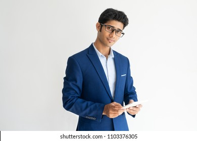Portrait of confident businessman in glasses with smartphone. Young Indian manager wearing blue jacket using mobile phone and looking at camera. Successful businessman concept