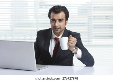 Portrait of confident businessman having coffee while working in office
