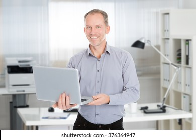 Portrait of confident businessman holding laptop while standing in office