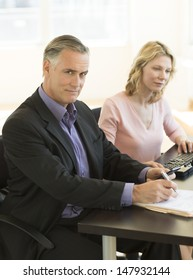 Portrait of confident businessman holding mobile phone and pen with colleague working in office