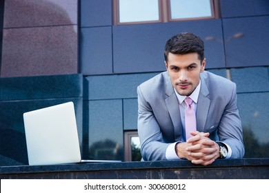 Portrait of a confident businessman with laptop computer outdoors. Looking at camera