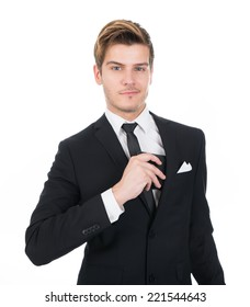 Portrait of confident businessman putting wallet in his pocket against white background