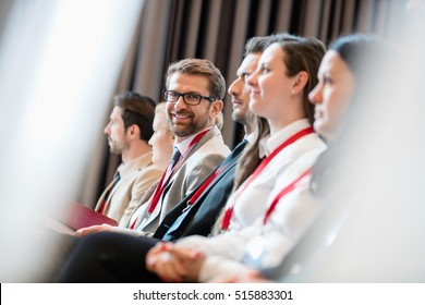 Portrait of confident businessman sitting in seminar hall