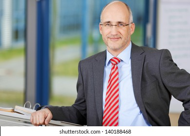 Portrait of confident businessman smiling while leaning on podium in office