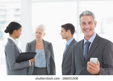 Portrait of confident businessman using a smartphone with colleagues behind in office
