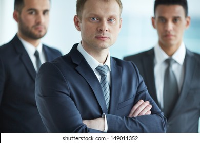 Portrait of confident businessmen looking at camera with young leader in front