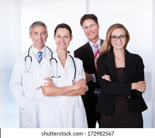 Portrait Of Confident Businesspeople And Medical Workers Standing Together