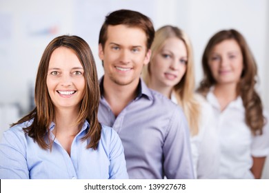 Portrait of confident businesspeople standing in a row at office