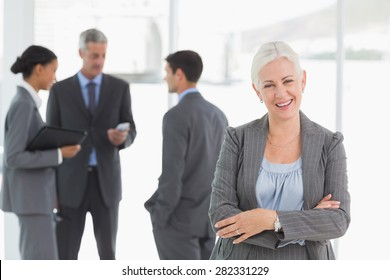 Portrait of confident businesswoman with colleagues behind in office