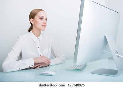 Portrait of confident businesswoman looking at computer while working in office