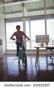 Portrait of confident businesswoman riding bicycle in creative office