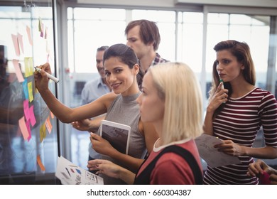 Portrait of confident businesswoman with team planning in creative office