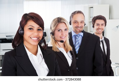 Portrait of confident call center representatives smiling in office