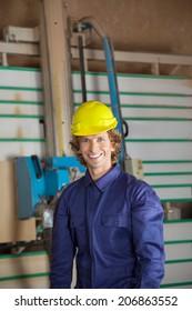 Portrait of confident carpenter standing against vertical saw machine in workshop