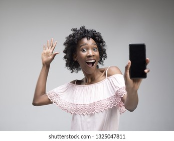 Portrait of a confident casual african american girl showing blank screen of mobile phone isolated over gray background at studio.