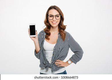 Portrait of a confident casual girl showing blank screen mobile phone isolated over white background
