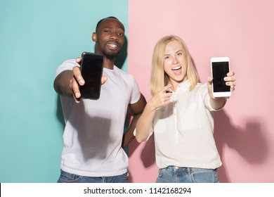 Portrait of a confident casual girl showing blank screen mobile phone isolated over pink and blue background. Blond girl with freckles and afro man