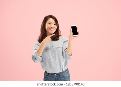 Portrait of a confident casual girl showing blank screen mobile phone isolated over pink background.