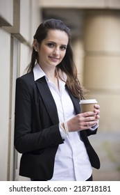 Portrait of a confident caucasian business woman standing outdoors in modern urban setting.