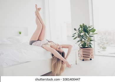 Portrait of confident, charming, sexy, pretty, successful, stylish girl in nightwear lying on back with legs up, enjoying time at home alone, having nice mood in the morning