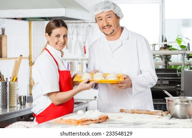 Portrait of confident chefs holding pasta tray in commercial kitchen