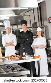 Portrait of confident chefs standing with arms crossed in industrial kitchen