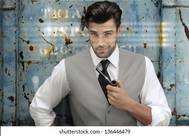 Portrait of a confident classically handsome male model holding a pipe in upscale clothing