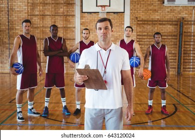 Portrait of confident coach and basketball player standing in the court
