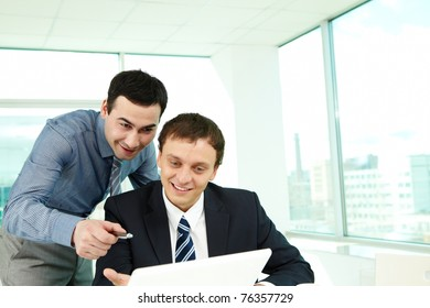 Portrait of confident colleagues looking at laptop screen in office