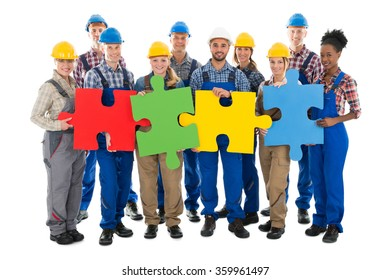 Portrait of confident construction workers joining jigsaw pieces against white background