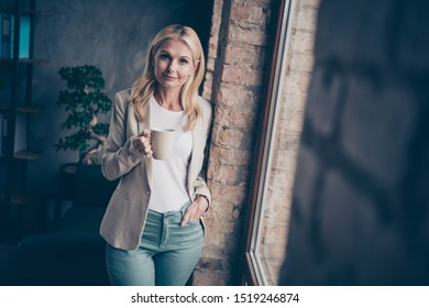 Portrait of confident cool smart middle aged businesswoman hold cup mug with espresso have break relax promotion wear style beige jacket stand near window in company office
