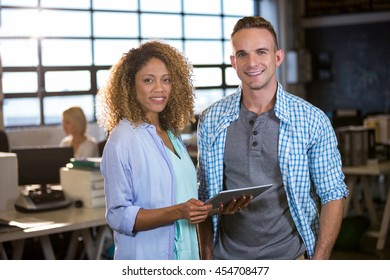 Portrait of confident coworkers standing in creative office