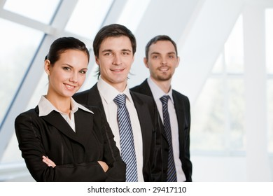 Portrait of confident co-workers standing in line with pretty employer in front