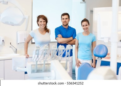 Portrait of confident dental surgeon and assistants in dentist's office.