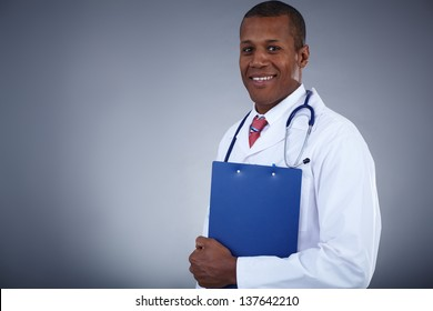 Portrait of confident doctor with clipboard looking at camera