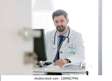 Portrait of confident doctor using computer at desk in hospital