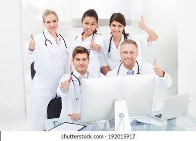 Portrait of confident doctors gesturing thumbs up at desk in clinic