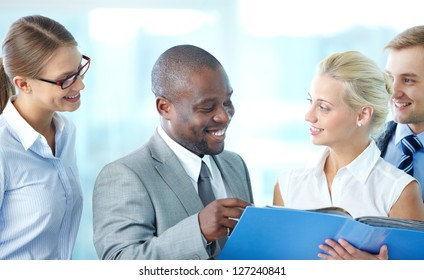 Portrait of confident employees discussing document at meeting